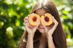 young girl holds peaches on eyes