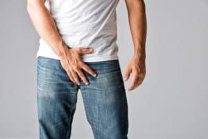 man grabbing his crotch